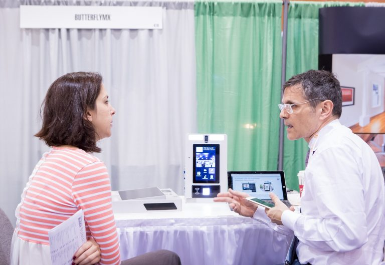 A one-on-one meeting takes place in the ButterflyMX booth during the 2017 TecHome Builder Summit.
